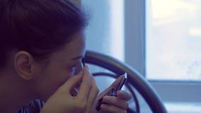 A mulher põe a composição, pinta suas sobrancelhas com uma escova na frente de um espelho pequeno video estoque