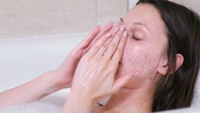 A mulher põe esfrega na cara que encontra-se no banheiro Enfrente o close-up
