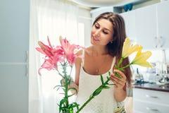 A mulher põe flores dos lírios no vaso Dona de casa que toma do aconchego e da decora??o na cozinha Ramalhete de composi??o fotos de stock