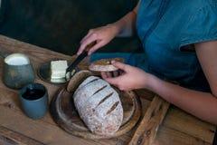 A mulher põe a manteiga sobre o conceito do café da manhã do pão de centeio Imagens de Stock Royalty Free
