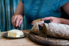 A mulher põe a manteiga sobre o conceito do café da manhã do pão de centeio Imagens de Stock