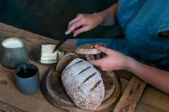 A mulher põe a manteiga sobre o conceito do café da manhã do pão de centeio Foto de Stock