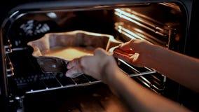 A mulher põe o bolo no forno vídeos de arquivo