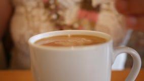A mulher põe o creme em seu café e as agitações com colher video estoque