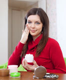 A mulher põe o creme sobre a cara em sua casa Imagem de Stock Royalty Free