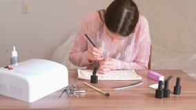 A mulher põe o primeiro revestimento da goma-laca cor-de-rosa sobre seus pregos com borla pequena filme