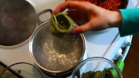 A mulher põe os espaguetes na água a ferver sob a forma dos ninhos, com espinafres filme