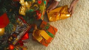 A mulher põe sob o presente da árvore de Natal no pacote dourado video estoque