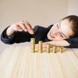 A mulher põe uma moeda sobre a tabela Foto de Stock