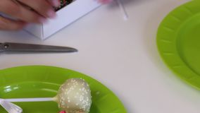 A mulher p?e PNF do bolo em uma caixa de presente Os doces s?o decorados com um molho diferente da cor e curvas da fita Tesouras  filme