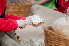 A mulher pôs a pasta sobre o pão da lareira Festival medieval do ar livre fotos de stock