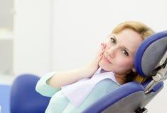 A mulher paciente no dentista queixa-se da dor de dente foto de stock