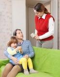 A mulher paga o baby-sitter por seu bebê Fotografia de Stock Royalty Free