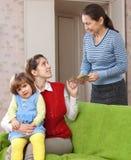 A mulher paga o baby-sitter por sua criança Fotos de Stock Royalty Free