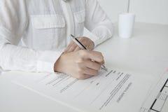 Mulher para assinar um contrato com uma pena Imagem de Stock