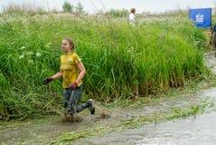 A mulher participa na raça através dos campos Tyumen Fotos de Stock Royalty Free