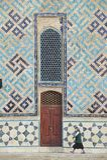 A mulher passa pela parede do mausoléu de Khoja Ahmed Yassawi em Turkistan, Cazaquistão Imagem de Stock