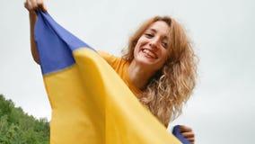 A mulher patriótica nova está guardando a bandeira ucraniana azul e amarela sobre o fundo do céu ao comemorar visto-livre video estoque