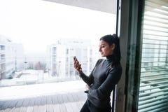Mulher pela janela que guarda o smartphone imagem de stock royalty free