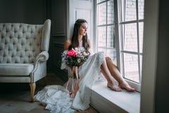 Mulher pelo indicador Noiva que olha para fora a janela, espera o noivo Fotos de Stock Royalty Free