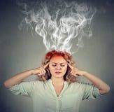 A mulher pensa muito intensamente tendo a dor de cabeça imagem de stock