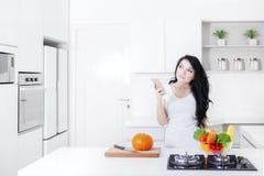 Mulher pensativa com o smartphone na cozinha imagens de stock