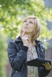 Mulher pensativa com a tabuleta digital que olha acima Foto de Stock