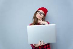 Mulher pensativa do moderno que está com portátil imagem de stock