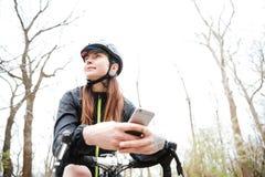 Mulher pensativa na bicicleta com telefone celular no parque Fotografia de Stock Royalty Free