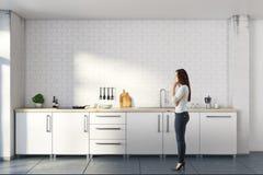 Mulher pensativa na cozinha branca Imagem de Stock