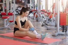 A mulher pensativa no sportswear que senta-se na esteira após o treinamento no gym, tem o resto após dá certo, parecendo cansa fotos de stock