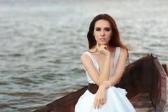 Mulher pensativa no vestido branco que senta-se em um barco velho Fotografia de Stock