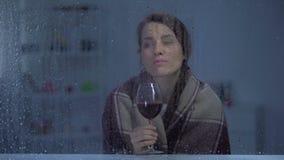 Mulher pensativa no vinho bebendo geral atrás da janela chuvosa, noite fria video estoque