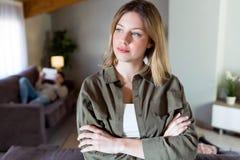 Mulher pensativa nova bonita com os braços cruzados e que olham lateralmente em casa imagem de stock