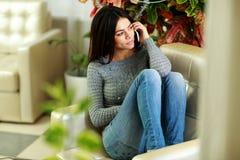 Mulher pensativa nova que fala no telefone e que olha afastado foto de stock