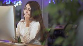 Mulher pensativa nova que senta-se em seu local de trabalho na frente do computador moderno no escritório que datilografa no tecl video estoque