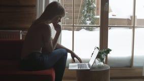 Mulher pensativa nova que senta-se no sofá ao datilografar e ao ler email no portátil com fundo do inverno na janela fotografia de stock