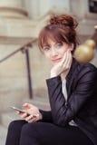 Mulher pensativa que guarda seu móbil Fotografia de Stock