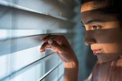 Mulher pensativa que olha através das cortinas de janela foto de stock
