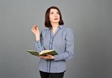 Mulher pensativa que olha ausente ao pensar Escreva em suas notas Foto de Stock Royalty Free