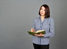 Mulher pensativa que olha ausente ao pensar Escreva em suas notas Fotos de Stock