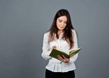 Mulher pensativa que olha e que escreve em suas notas Imagem de Stock Royalty Free