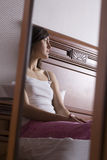 Mulher pensativa que reflete no espelho no quarto Fotografia de Stock Royalty Free