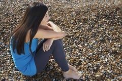 Mulher pensativa que senta-se em seixos na praia fotografia de stock