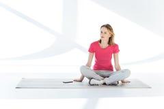 Mulher pensativa que senta-se na esteira da ioga com smartphone e que olha afastado imagem de stock royalty free