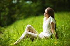 Mulher pensativa que senta-se na grama imagem de stock