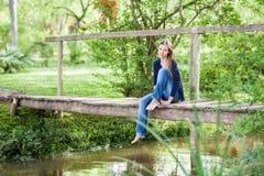 Mulher pensativa que senta-se na ponte de madeira Fotografia de Stock