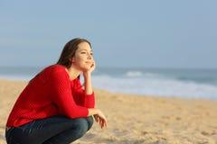 Mulher pensativa segura que pensa na praia imagem de stock