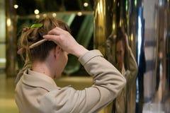 A mulher penteia seu cabelo Fotografia de Stock Royalty Free