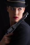 Mulher perigosa no preto com revólver de prata Fotografia de Stock Royalty Free